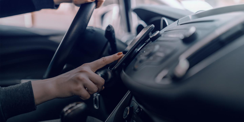 Une femme au volant de sa voiture appuie sur son téléphone pour suivre sa geolocalisation